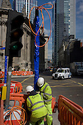 Two construction workmen manhandle a new post on Bishopsgate (Street) in the City of London, the capital's financial district.