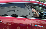Motorist take cell phone photos as they drive past the make shift memorial in front of the Emanuel AME Church, Friday, June 19, 2015 in Charleston, S.C. The church was the scene of a shooting Wednesday night where Dylann Storm Roof killed nine people including a state representative Rev. Clementa C. Pinckney who was the pastor of the church. (AP Photo/Stephen B. Morton)