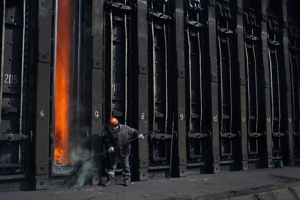 A worker shovels cokes back into a furnace at the Metinvest Coke Plant on March 18, 2015 in Avdiivka, Ukraine. Shells have hit the property of the plant over 150 times, including multiple hits on the plant itself.