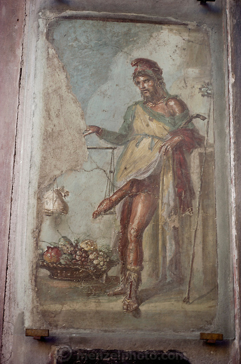 Old fresco in the ruins of Pompeii of a man weighing his penis on a scale. Pompeii, Italy.