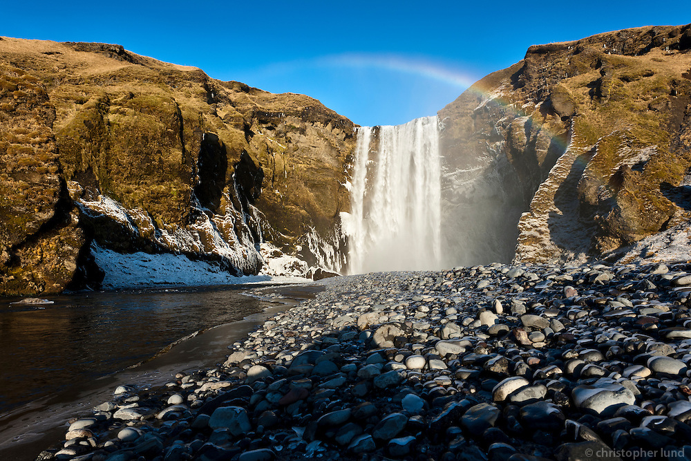 Skógafoss waterfall in South Iceland. Warm february winter light. Rainbow above fall.