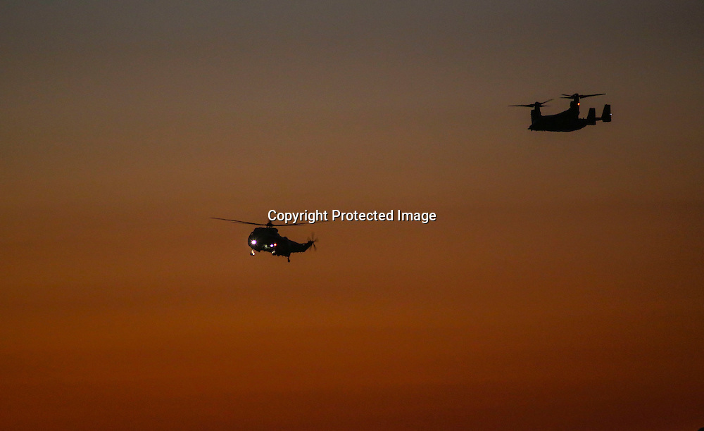 "Marine One, left, with President Barack Obama aboard, is escorted by  an ""Osprey"" aircrafts as it arrives at  Los Angeles International Airport in Los Angeles on Saturday, Oct. 10, 2015.  (AP Photo/Ringo H.W. Chiu)"