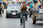 21 FEBRUARY 2014 - KHLONG CHIK, PHRA NAKHON SI AYUTTHAYA, THAILAND: A man rides a bike between farmers' tractors blocking Highway 32 near Bang Pa In in Phra Nakhon Si Ayutthaya province. About 10,000 Thai rice farmers, traveling in nearly 1,000 tractors and farm vehicles closed the road. The farmers were traveling to the airport in Bangkok to protest against the government because they haven't been paid for rice the government bought from them last year. The farmers turned around and went home after they met with government officials who promised to pay the farmers next week. This is the latest blow to the government of Yingluck Shinawatra which is confronting protests led by anti-government groups, legal challenges from the anti-corruption commission and expanding protests from farmers who haven't been paid for rice the government bought.    PHOTO BY JACK KURTZ