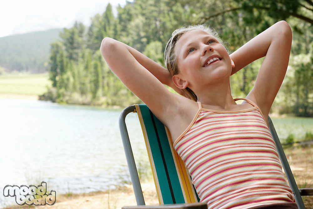 Girl (7-9) by lake leaning back on deck chair.
