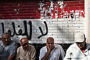 """Egyptian men cue in front of a polling station in the last few minutes before the start of the first truly democratic Presidential election in Egypt's history May 23, 2012 in Cairo, Egypt. Graffiti behind the men translates to """"No felool"""", a reference to members of Mubarak's former government and National party members. The election will take place over two days, May 23, and 24th 2012.  (Photo by Scott Nelson)"""