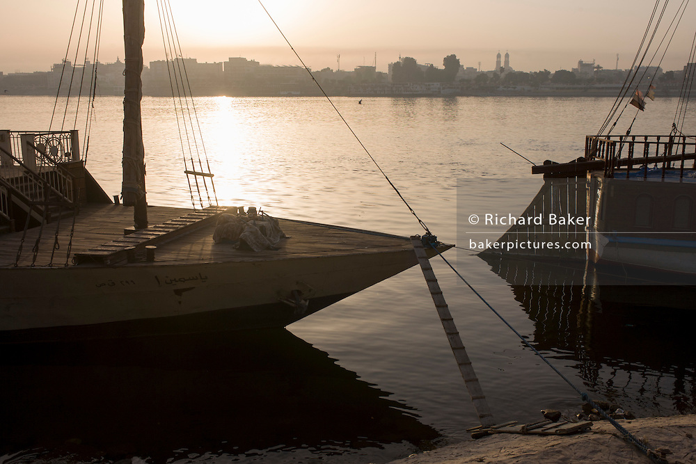Assorted boats are moored at dawn on the West Bank of the river Nile in Luxor, Nile Valley, Egypt.
