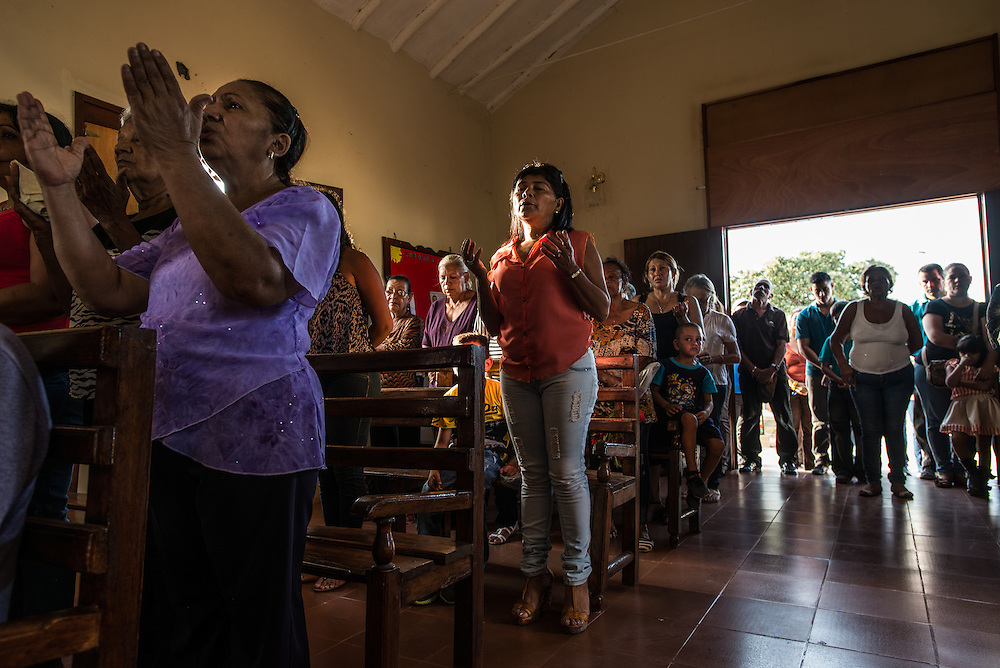 """LA VELA, VENEZUELA - SEPTEMBER 12, 2016: Florangel Amaya de Ramos (center) attends mass to pray for her missing son, Jesús Ramos who disappeared after leaving with a smuggler and other migrants to travel illegally and look for work in Curaçao. Jesús knew he would have to swim ashore from the smuggler's boat. So he spent his last weeks in Venezuela doing laps in the sea in front of his home in La Vela, his mother recalls. But the boat carrying the men never made it - it vanished somewhere off the coast of Venezuela last year. No wreckage was found. The only evidence that their journey even occurred is a few selfies sent from their smartphones just before they departed. The men posed on the side of the skiff with big smiles. """"I try not to cry — I tell myself, 'he's well, that's it,'"""" said Ms. Ramos. Questions haunt the families of the lost migrants each time they look out toward the sea. Could the men still be alive somehow? Are these journeys worth it? Will Venezuela ever return to the country that it was, one where it was not necessary to swim to the shore in Curaçao after being tossed from a fishing boat? Ms. Ramos is still waiting for her son and speaks of him in the present tense. Each Monday, she goes to Mass to pray for his return.""""I always speak to God,"""" said Ms. Ramos. """"I am always looking up at that picture of the Virgin. I am scared one day she will yell back at me, 'Enough, already. That's enough.'"""" PHOTO: Meridith Kohut for The New York Times"""