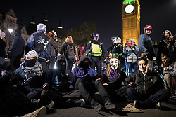 © Licensed to London News Pictures . 05/11/2016 . London , UK . Protesters sit in and block the road outside Parliament . Supporters of Anonymous , many wearing Guy Fawkes masks , attend the Million Mask March bonfire night demonstration , in central London . Photo credit : Joel Goodman/LNP