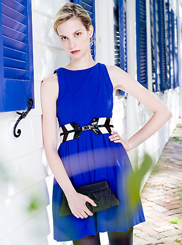 Fashion image, female against white wall with blue shutters
