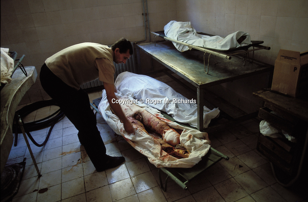 A morgue attendant adjusts the body of a man killed by a Serb artillery shell during the Bosnian Serb siege of Sarajevo, Bosnia and Herzegovina, summer 1992. Almost 2,000 children, and over 10,000 people in total were killed in Sarajevo during the 3-1/2 year siege. (Photo by Roger Richards)
