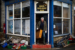 © Licensed to London News Pictures. 29/12/2015. York, UK. Ruined stock and belongings lie on the street as CHAZ BURNS removes a damaged cupboard drawer from his fishing tackle shop,  which was badly damaged by flood waters, on Huntington Road in York. Further rainfall is expected over coming days as Storm Frank approaches the east coast of the country. Photo credit: Ben Cawthra/LNP
