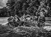 Fleuve Oyapock, Guyane, 2015.<br /> <br /> Pirogue am&eacute;rindienne. Une famille de Trois-Sauts descend le fleuve jusqu&rsquo;&agrave; Saint-Georges. <br /> Pour les habitants isol&eacute;s des villages de Trois-Sauts, tout est cher. Le co&ucirc;t du transport pour se rendre &agrave; Camopi ou &agrave; Saint-Georges est un r&eacute;el handicap dans le budget des familles d&eacute;pendant du Revenu de Solidarit&eacute; Active.<br /> L&rsquo;octroi des allocations familiales ou des allocations de parent isol&eacute; est naturellement devenu un &eacute;l&eacute;ment moteur du taux de natalit&eacute;.  <br /> <br /> Les rythmes scolaires sont ici diff&eacute;rents de ceux de Saint-Georges et du littoral. R&eacute;guli&egrave;rement, en p&eacute;riode de vacances scolaires les familles sont oblig&eacute;es de se descendre le fleuve pour r&eacute;cup&eacute;rer les ain&eacute;s scolaris&eacute;s au coll&egrave;ge de Saint-Georges.