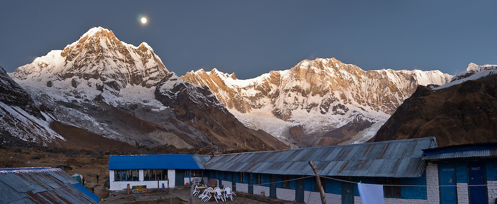 "The full Moon sets at dawn over Annapurna South (also known as Annapurna Dakshin, or Moditse; 23,684 feet / 7219 meters), as seen from Hotel Paradise Garden & Restaurant, at Annapurna South Base Camp (ABC, at 13,550 feet elevation), in the Himalaya of Nepal. On the right is Annapurna I (26,545 feet / 8091 meters elevation), the world's 10th ..highest peak. Annapurna is Sanskrit for ""Goddess of the Harvests."" In Hinduism, Annapurna is a goddess of fertility and agriculture and an avatar of Durga. (Panorama stitched from 3 images.)"