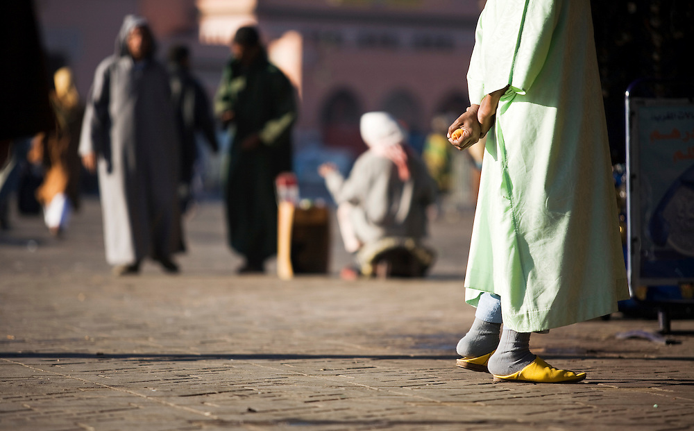A man wearing traditional Moroccan slippers and a green robe holds the leftovers of his breakfast in Djemaa el Fna, the central square of Marrakech. The central square of Marrakech is full of tourists and stalls.