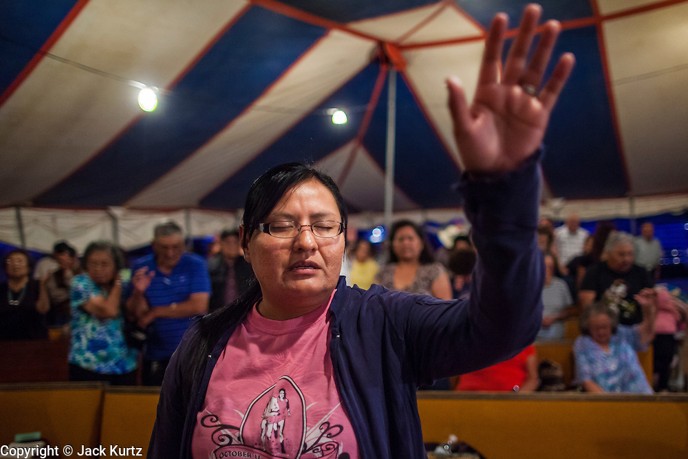 """12 JULY 2012 - FT DEFIANCE, AZ:   A woman prays at the 23rd annual Navajo Nation Camp Meeting in Ft. Defiance, north of Window Rock, AZ, on the Navajo reservation. Preachers from across the Navajo Nation, and the western US, come to Navajo Nation Camp Meeting to preach an evangelical form of Christianity. Evangelical Christians make up a growing part of the reservation - there are now more than a hundred camp meetings and tent revivals on the reservation every year. The camp meeting in Ft. Defiance draws nearly 200 people each night of its six day run. Many of the attendees convert to evangelical Christianity from traditional Navajo beliefs, Catholicism or Mormonism. """"Camp meetings"""" are a form of Protestant Christian religious services originating in Britain and once common in rural parts of the United States. People would travel a great distance to a particular site to camp out, listen to itinerant preachers, and pray. This suited the rural life, before cars and highways were common, because rural areas often lacked traditional churches.  PHOTO BY JACK KURTZ"""