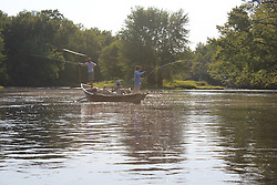 Streamer fishing in a drift boat for muskie in Hayward, Wisconsin. Fly lines shining in the late afternoon sun.