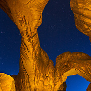 Window Arch lit with headlamp with the night sky and star trails of the moving earth near Moab, Utah.