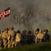 Confederate troops, bottom, fire on Union positions during the sunrise  battle on Saturday during the weekend-long Battle of Perryville, a national  Civil War Reenactment, in Perryville, Ky., on 10/5/02. The sunrise battle  depicts the opening attack of Daniel Donelson's Confederate Brigade against  the center of the Union First Corps.