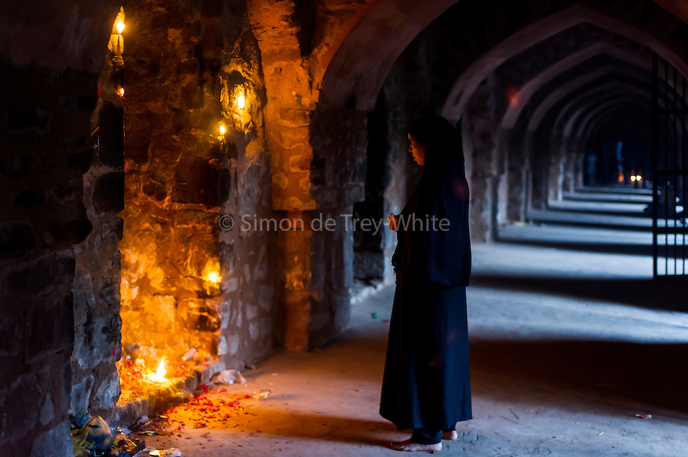 13th August 2015, New Delhi, India.  A woman stands before a shrine to Djinns in the ruins of Feroz Shah Kotla in New Delhi, India on the 13th August  2015. <br /> <br /> A polished sandstone pillar from the 3rd century B.C., one of many pillars of Ashoka left by the Mauryan emperor was moved from Pong Ghati Ambala, Punjab (currently in Haryana) to Delhi under orders of Firoz Shah Tughlaq of Delhi Sultanate, and re-erected in its present location in 1356, it sits atop of a three-tiered arcaded pavilion.<br /> <br /> PHOTOGRAPH BY AND COPYRIGHT OF SIMON DE TREY-WHITE a photographer in delhi<br /> + 91 98103 99809. Email: simon@simondetreywhite.com<br /> <br /> People have been coming to Firoz Shah Kotla to pray to and leave written notes and offerings for Djinns in the hopes of getting wishes granted since the late 1970's. Jinn, jann or djinn are supernatural creatures in Islamic mythology as well as pre-Islamic Arabian mythology. They are mentioned frequently in the Quran  and other Islamic texts and inhabit an unseen world called Djinnestan. In Islamic theology jinn are said to be creatures with free will, made from smokeless fire by Allah as humans were made of clay, among other things. According to the Quran, jinn have free will, and Iblīs abused this freedom in front of Allah by refusing to bow to Adam when Allah ordered angels and jinn to do so. For disobeying Allah, Iblīs was expelled from Paradise and called &quot;Shayṭān&quot; (Satan).They are usually invisible to humans, but humans do appear clearly to jinn, as they can possess them. Like humans, jinn will also be judged on the Day of Judgment and will be sent to Paradise or Hell according to their deeds. Feroz Shah Tughlaq (r. 1351&ndash;88), the Sultan of Delhi, established the fortified city of Ferozabad in 1354, as the new capital of the Delhi Sultanate, and included in it the site of the present Feroz Shah Kotla. Kotla literally means fortress or citadel.
