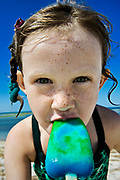 Girl eating a popsicle at the beach.