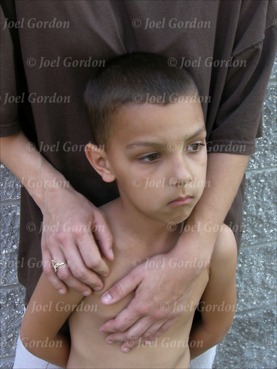 Homeless mother with arms and hands holding her 6 year old son, 29 yr old, single mother with 3 children, she is homeless trying to keep a stable home and job, now living in Orlando Union Rescue Mission Shelter for women and child.<br /> <br /> release # 1816