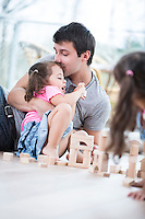 Loving father kissing daughter building blocks on floor