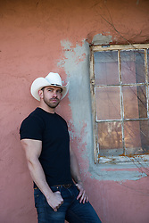 sexy cowboy leaning against a wall