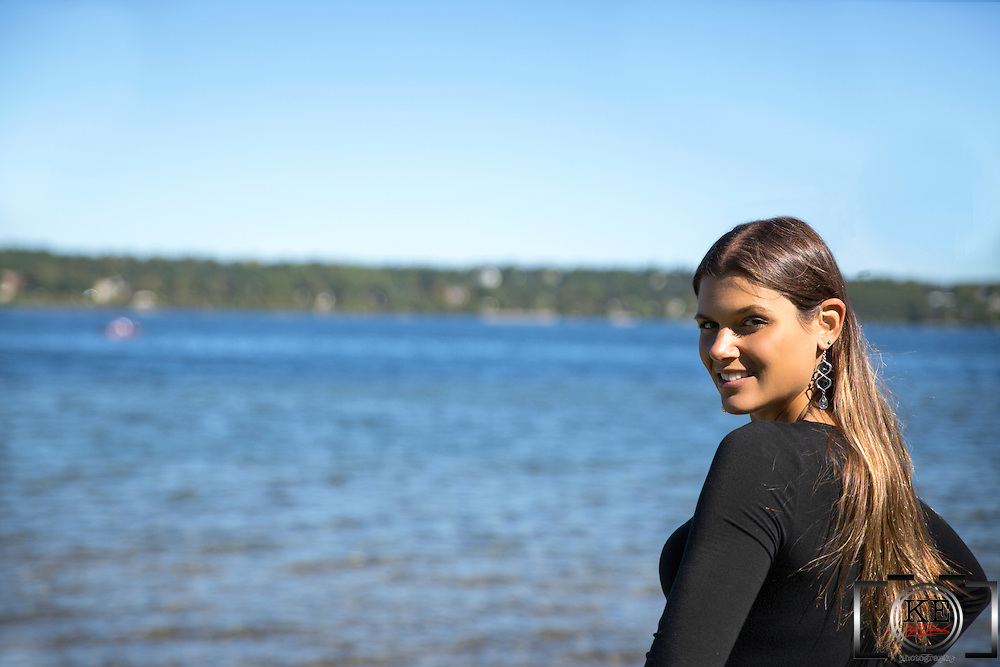 A young lady, standing by the lake, looking back over her shoulder.