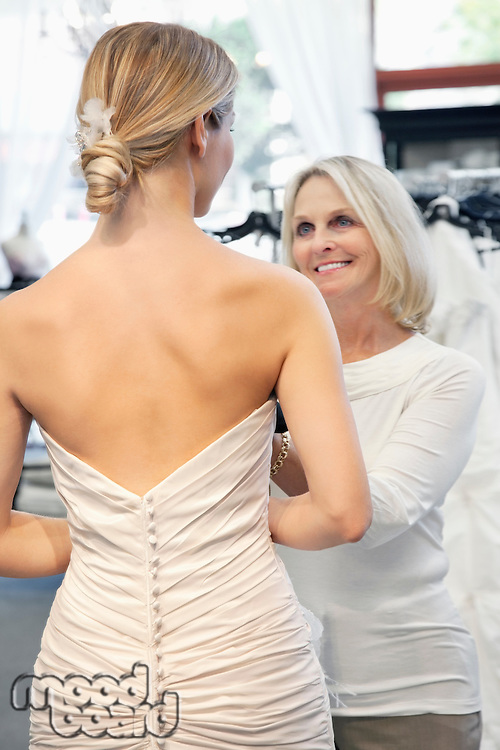 Back view of woman dressed in bridal gown with happy senior owner assisting