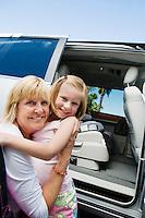 Mother Hugging Daughter by Minivan