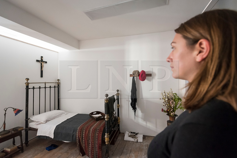 """© Licensed to London News Pictures. 13/11/2018. LONDON, UK. A staff member stands in Ruth Ellis' prison cell.  Preview of """"Glad I Did It"""", a new work by Irish artist Christina Reihill at Bermondsey Project Space.  The interactive artwork looks at the life and death of Ruth Ellis, the last woman to be hanged in Britain, after she shot her lover, racing driver, David Blakely in 1955.  On display are the artist's interpretation of Ruth Ellis' prison cell, including furniture and props, the hanging room together with a video display of the artist in conversation.   The show runs 14 November to 1 December 2018.  Photo credit: Stephen Chung/LNP"""