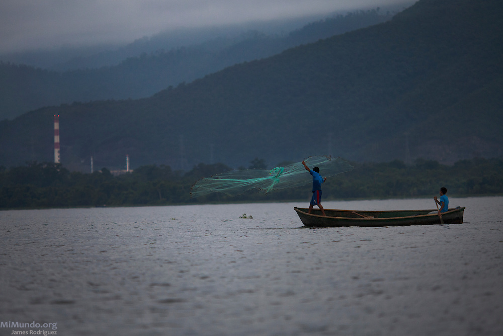 Two young men fish at dawn in Lake Izabal near the Fenix nickel mining project in El Estor, Guatemala. Established in 1965 as the EXMIBAL mine owned by Canadian mining firm INCO, the project was transferred to the Guatemalan Nickel Company (CGN) in 2005 after the expiration of the original 40-year license. CGN was the local subsidiary of Canadian Skye Resources, a junior mining company comprised of former INCO directors, until Canadian HudBay Minerals acquired Skye Resources in 2008. Russian-based Solway Group bought the mine in 2011. The Fenix project, marred with numerous human rights issues throughout its history, began formal processing operations in May 2014. El Estor, Izabal, Guatemala. September 28, 2014.