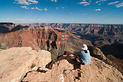 A man sits on the north rim of the Grand Canyon at Point Sublime, contemplating the grandeur