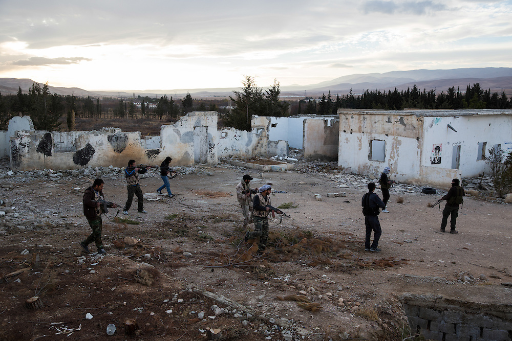 A group of FSA fighters guarding one of the entrances to Yabroud in a camp captured in December 2011. On the wall pictures of Hafez Bachar.<br /> <br /> Photo: Niclas Hammarstr&ouml;m