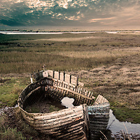 Decaying timber fishing boat resting on marshland in water at Blakeney in North Norfolk, England