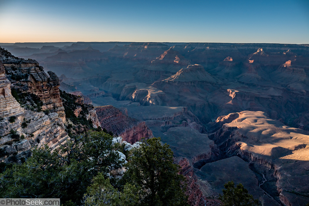Red ridges rise in blue haze at sunset seen from Mather Point Overlook, Grand Canyon National Park, Arizona, USA. Starting at least 5 to 17 million years ago, erosion by the Colorado River has exposed a column of distinctive rock layers, which date back nearly two billion years at the base of Grand Canyon. While the Colorado Plateau was uplifted by tectonic forces, the Colorado River and tributaries carved Grand Canyon over a mile deep (6000 feet), 277 miles  long and up to 18 miles wide.
