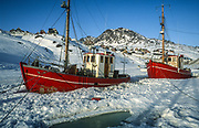 Fishing boats frozen into Ammassalik harbour, Eastern Greenland, start point for  dog sledging and skiing across Greenland icecap, Arctic