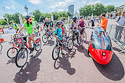 The riders pass Buckingham Palace and are fascinated by a red carbon fibre aerodynamic ticycle - Prudential RideLondon a festival of cycling, with more than 95,000 cyclists, including some of the world's top professionals, participating in five separate events over the weekend of 1-2 August.