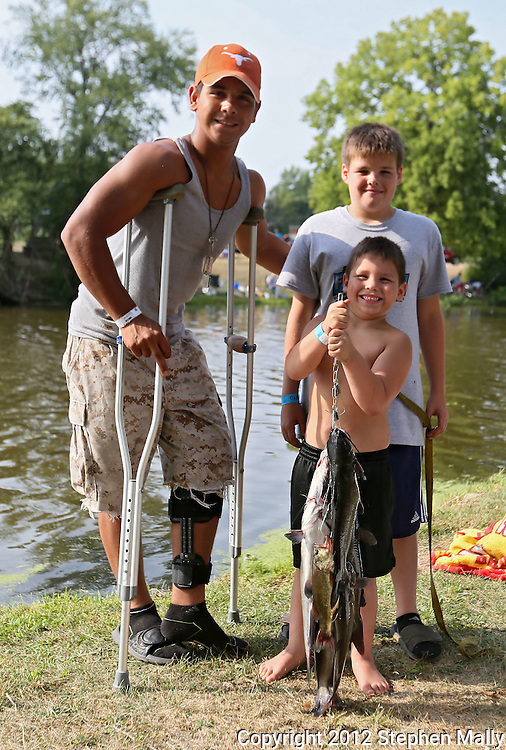 John Saldival (from left), 15, Chase Saldival, 12, and Xander Saldival, 6, all of Cedar Rapids, stand by their fish during the 10th annual Boys & Girls Clubs of Cedar Rapids Fish-O-Rama at Robbins Lake in Cedar Rapids on Saturday, August 4, 2012. Organizers expected 1,200-1,500 participants in the weekend event. There were 426 prizes available to people who caught tagged fish. Prizes included a Toyota truck, boat, TVs, grills, bicycles, and gift certificates.