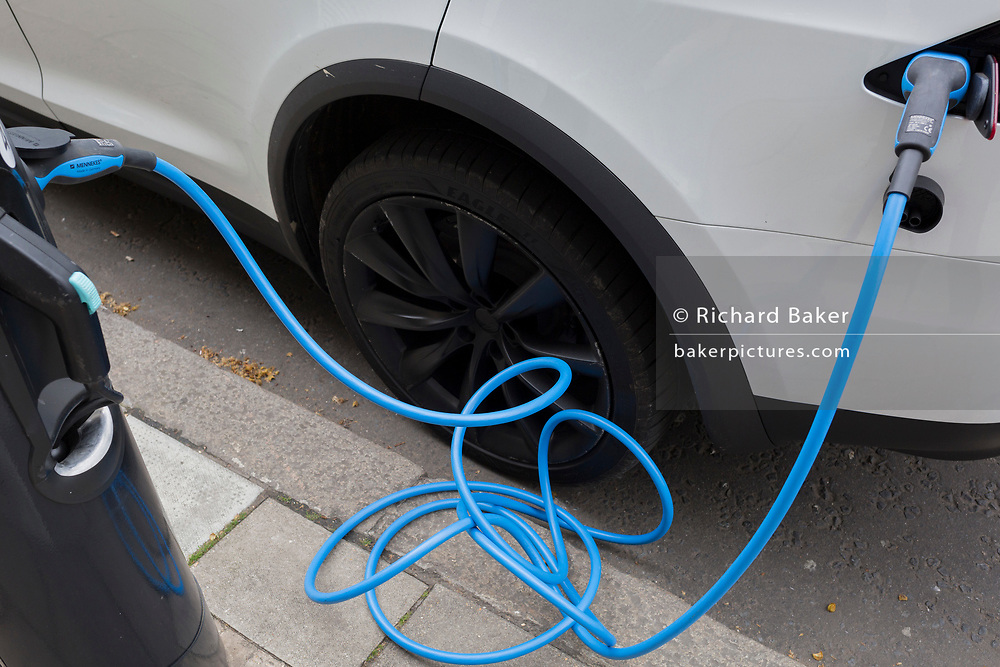 A twisted blue electric recharging cable is plugged in to a white car on a central London street, on 16th April 2018, in London, England.