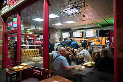"""© Licensed to London News Pictures . 17/12/2016 . Manchester , UK . People queue for food at a takeaway on Deansgate . Revellers out in Manchester City Centre overnight during """" Mad Friday """" , named for being one of the busiest nights of the year for the emergency services in the UK . Photo credit : Joel Goodman/LNP"""