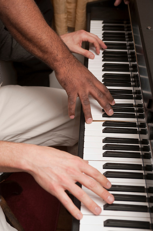 Hands on a piano keyboard