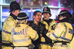 """© Licensed to London News Pictures . 20/12/2014 . Manchester , UK . Police tend to a vomiting man with a head injury outside Deansgate Locks nightclub venue . An ambulance took over 40 minutes to arrive . """" Mad Friday """" revellers out in the rain and cold in Manchester . Mad Friday is typically the busiest day of the year for emergency services , taking place on the last Friday before Christmas when office Christmas parties and Christmas revellers enjoy a night out .  Photo credit : Joel Goodman/LNP"""
