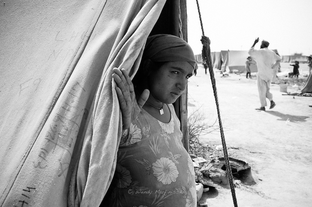 Hamida opens up their tent after heavy winds have calmed down. Karachi, Pakistan, 2010