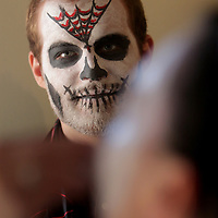 Jacob Huber watches Anna Gamel paint Caroline Park's face at Flytrap Brewing during the Day of the Dead Art Crawl in the Brooklyn Arts District. (Jason A. Frizzelle)