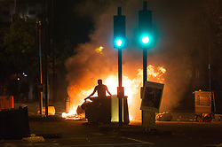"""© Licensed to London News Pictures. 28/07/2017. London, UK. Protesters take to the streets of Dalston setting mattress on fire as they clash with police following the death of Rashan Charles whilst being arrested by police.  A statement from Scotland Yard said Mr Charles went into a shop, where he was seen """"trying to swallow an object"""" and it was then police officers struggled with him to make an arrest. Photo credit: Ray Tang/LNP"""
