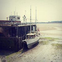 English seaside scene with small steamboat moored at key in summer at low tide
