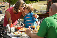 A family enjoys lunch on the outdoor patio of Merlins Restaurant, at the base of Blackcomb Mountain in Whistler, BC Canada