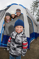 Boy with family in front of tent, portrait