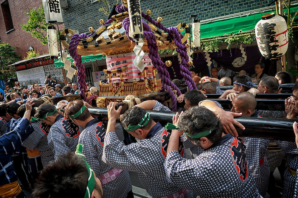 Pilgrims carry a mikoshi or divine palanquin during a Japanese festival. Sanja Matsur (Three Shrine Festival), is an annual Shinto festival held in Tokyo. The earliest form of the festivals dates back to the 7th century CE and is held in honor of Hinokuma Hamanari, Hinokuma Takenari and Hajino Nakatomo, the three men who established and founded Sensō-ji temple. Sanja Matsuri is held on the third weekend of every May at Asakusa Shrine. Its  parades revolve around three mikoshi (three portable shrines referenced in the festival's name), as well as traditional music and dancing.